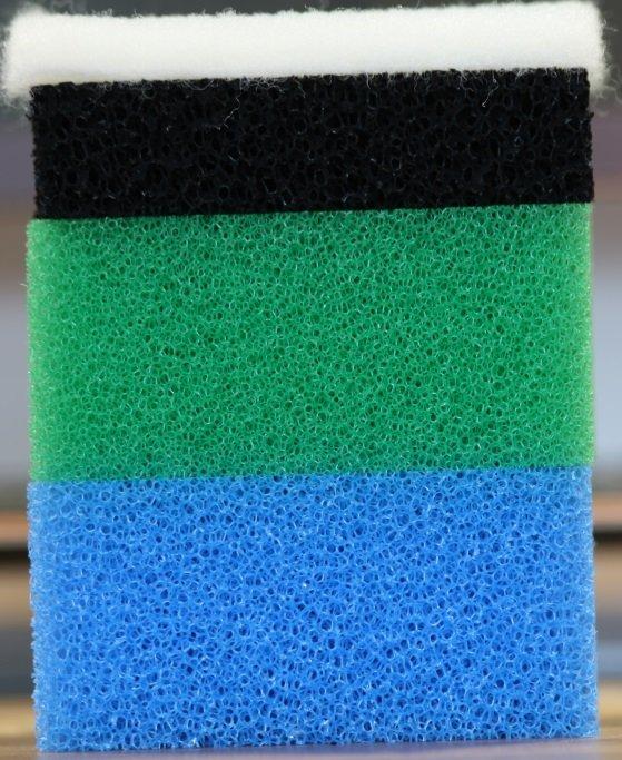 Ein Paket aus verschiedenen Filterelementen für einen Aquarium Filter. Oben befindet sich ein mechanischer Vorfilter aus Watte, gefolgt von einem chemischen Aktivkohlefilter. Die beiden unteren Schwämme dienen als biologischer Filter.