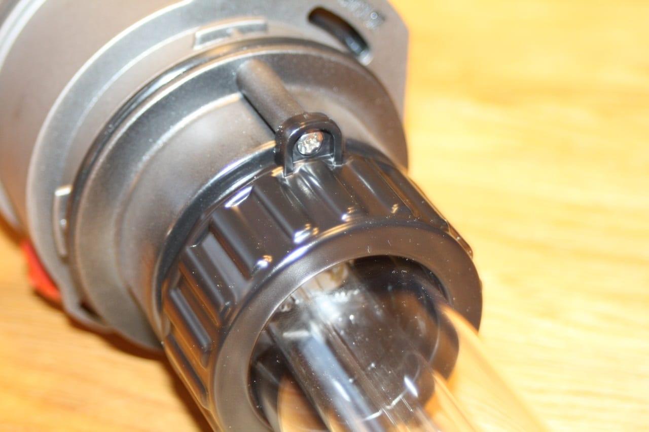 Der Glaskolben um den Brenner ist mit einer großen Überwurfmutter befestigt. Diese wird mit einer kleinen Schraube gegen selbsttätiges Lösen gesichert.