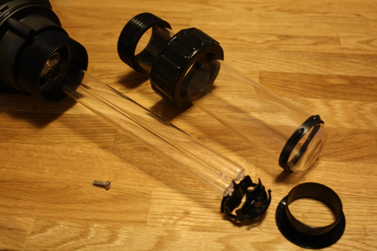Die Einzelteile des demontierten JBL ProCristal UV-C 11 W. Ein kleines Blechteil zentriert den Brenner im Glaskolben. Der Gummiring schützt den Glaskolben während der Montage.